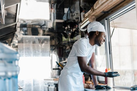 Photo for Selective focus of cheerful african american chef smiling in food truck - Royalty Free Image