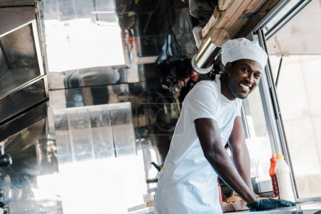 Photo for Selective focus of happy african american chef smiling in food truck - Royalty Free Image