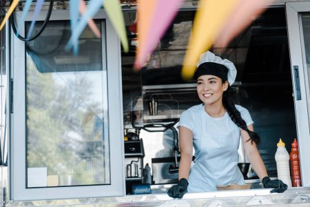 Photo for Selective focus of happy asian woman in hat and chef uniform smiling in food truck - Royalty Free Image
