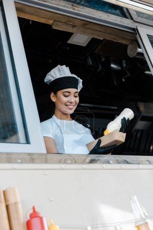 Photo pour Vue bas d'angle de femme asiatique gaie retenant la plaque de carton et la bouteille de mayonnaise dans le camion de nourriture - image libre de droit