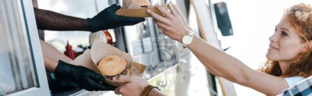 Photo for Panoramic shot of multicultural chefs giving carton plates with food to happy customers - Royalty Free Image