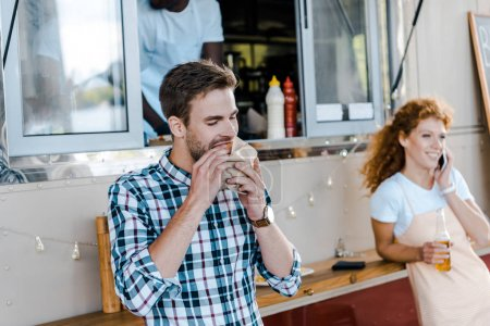 Photo for Selective focus of handsome man eating tasty burger near food truck - Royalty Free Image