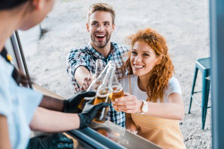 Photo for Selective focus of multicultural chefs toasting with bottles of beer near happy customers - Royalty Free Image
