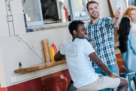 Photo for Selective focus of handsome men gesturing near african american friend and food truck - Royalty Free Image
