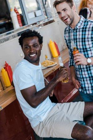 Photo pour Foyer sélectif des hommes multiculturels heureux tenant des bouteilles avec de la bière - image libre de droit