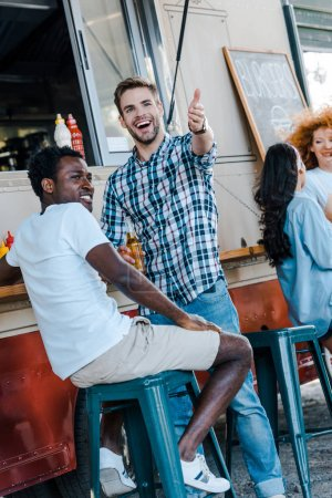 Photo for Selective focus of happy man gesturing near african american friend and food truck - Royalty Free Image