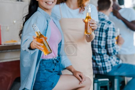 Photo for Cropped view of happy girls holding bottles of beer near food truck - Royalty Free Image