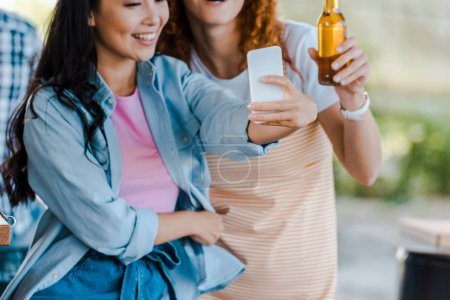 Photo for Cropped view of cheerful multicultural girls taking selfie near food truck - Royalty Free Image