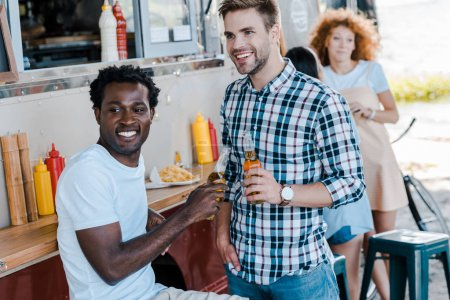 Photo for Selective focus of cheerful multicultural men holding bottles of beer near girls and food truck - Royalty Free Image