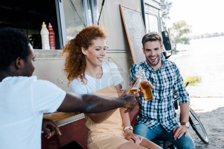 Photo pour Foyer sélectif de beaux hommes multiculturels clinquant avec des bouteilles de bière avec une femme rousse attrayante près du camion de nourriture - image libre de droit