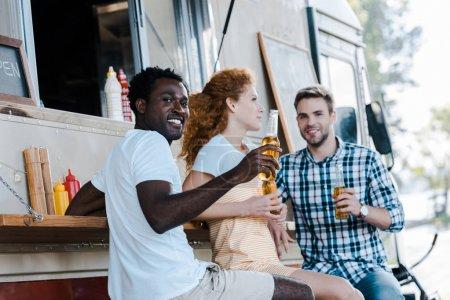 Foto de Enfoque selectivo de guapo hombre afroamericano sosteniendo botella de cerveza cerca de amigos - Imagen libre de derechos
