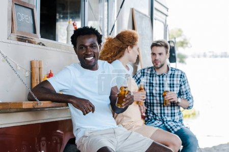 Photo for Selective focus of cheerful african american man holding bottle of beer near friends - Royalty Free Image