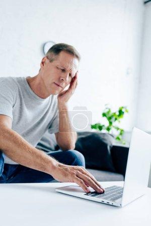 Photo pour Bel homme en t-shirt avec mal de tête en utilisant un ordinateur portable dans l'appartement - image libre de droit