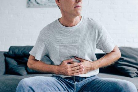 Photo pour Vue recadrée de l'homme en t-shirt avec mal d'estomac dans l'appartement - image libre de droit