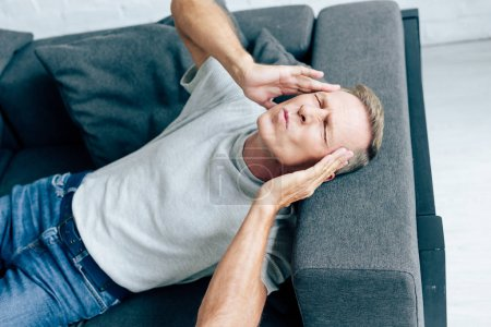 Photo for Handsome man in t-shirt with closed eyes touching head in apartment - Royalty Free Image