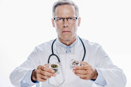 Photo pour Beau médecin en blouse blanche tenant le cannabis médical et les pilules isolées sur le blanc - image libre de droit
