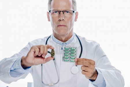 Photo for Handsome doctor in white coat holding medical marijuana and pills isolated on white - Royalty Free Image