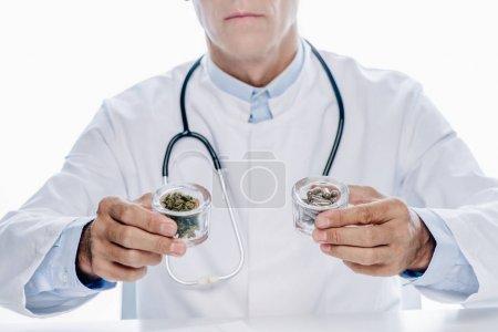 Photo pour Vue recadrée du docteur dans les pillules blanches de fixation de manteau et le cannabis médical isolésur le blanc - image libre de droit