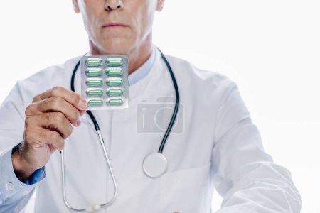 Photo pour Vue recadrée du docteur dans les pillules blanches de fixation de manteau d'isolement sur le blanc - image libre de droit
