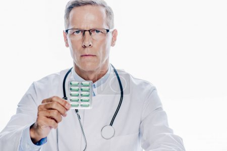 Photo for Handsome doctor in white coat holding pills isolated on white - Royalty Free Image
