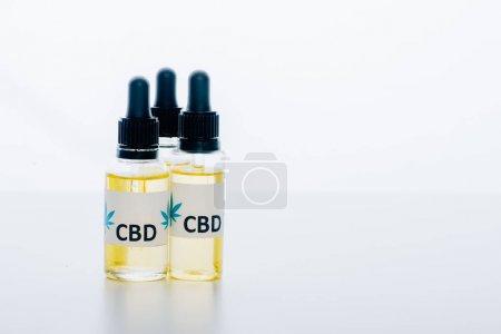 Photo pour Huile de cannabis dans des bouteilles avec le cbd de lettrage sur le fond blanc - image libre de droit