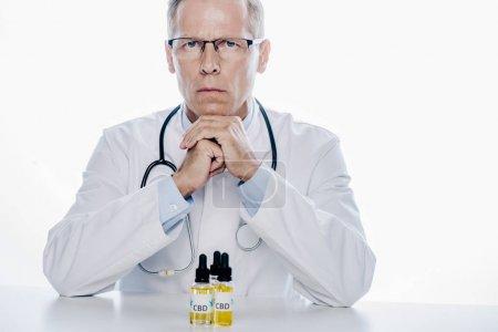 Photo pour Beau médecin en manteau blanc avec cbd sur la table isolé sur blanc - image libre de droit