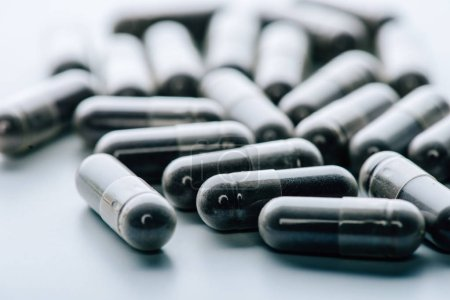 enfoque selectivo de las píldoras negras y oscuras sobre fondo blanco