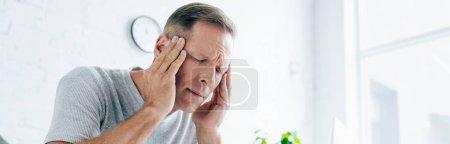 plano panorámico del hombre guapo con dolor de cabeza en el apartamento
