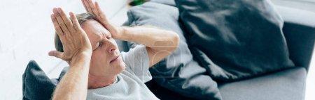 Photo pour Plan panoramique de bel homme avec mal de tête dans l'appartement - image libre de droit