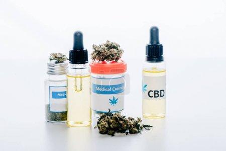 Photo pour Huile de cannabis dans des bouteilles avec le cbd de lettrage et le cannabis médical sur le fond blanc - image libre de droit