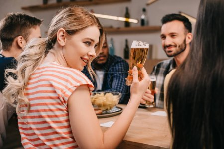 Photo for Selective focus of smiling young woman holding glass of beer while sitting with multicultural friends in pub - Royalty Free Image