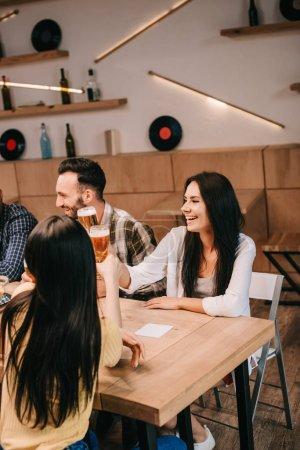 Foto de Jóvenes amigos clinking vasos de cerveza ligera mientras que pasar tiempo juntos en el pub - Imagen libre de derechos