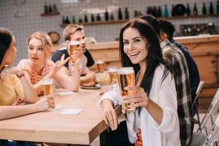 Foto de Joven alegre sosteniendo vidrio de cerveza ligera y mirando a la cámara mientras se sienta cerca de amigos en el pub - Imagen libre de derechos