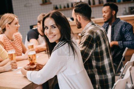 Foto de Atractiva joven sonriendo a la cámara mientras se sienta con amigos multiculturales juntos en el pub - Imagen libre de derechos