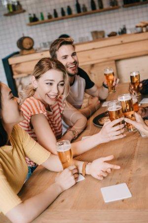 Photo pour Amis multiculturels heureux parler et faire des gestes tout en buvant de la bière dans le pub ensemble - image libre de droit