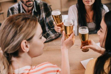 Foto de Vista recortada de amigos multiculturales clinking copas de cerveza ligera en el pub - Imagen libre de derechos