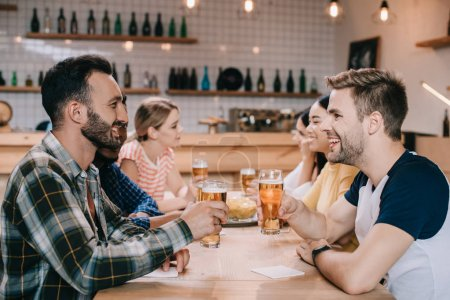 Photo for Cheerful multicultural friends talking and drinking light beer in pub - Royalty Free Image