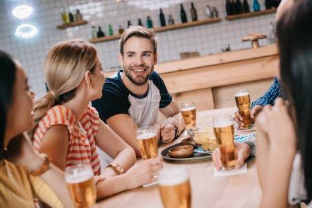 Foto de Amigos alegres hablando mientras pasan tiempo en el pub juntos - Imagen libre de derechos
