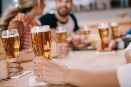 Photo for Cropped view of women holding glasses of light beer while sitting together with friends in pub - Royalty Free Image