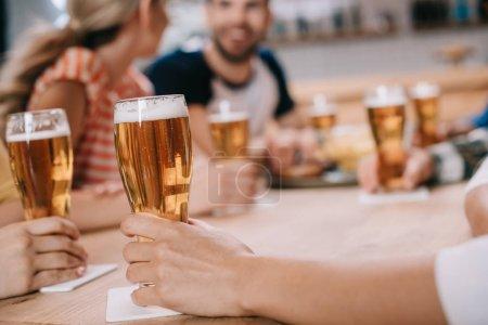 Foto de Vista recortada de las mujeres sosteniendo vasos de cerveza ligera mientras se sienta junto con amigos en el pub - Imagen libre de derechos