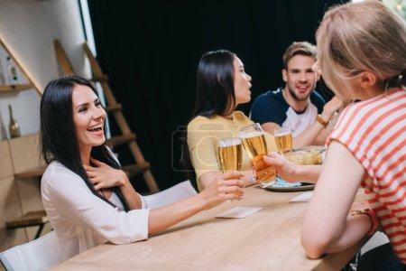 Foto de Joven alegre clinking gafas de cerveza ligera mientras se sienta en un pub con amigos multiculturales - Imagen libre de derechos