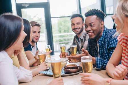 Photo for Cheerful multicultural friends talking while sitting together in pub - Royalty Free Image