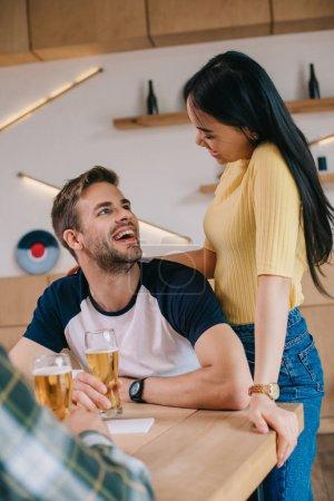 Foto de Joven mujer asiática de pie cerca de amigo sentado con un vaso de cerveza en el pub - Imagen libre de derechos