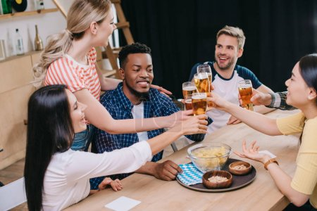 Photo pour Amis multiculturels joyeux clignotant des verres de bière légère dans le pub - image libre de droit