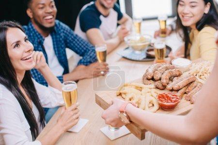 Photo pour Vue recadrée de plateau de fixation de femme avec des saucisses frites, des rondelles d'oignon et des frites français près des amis multiculturels heureux dans le bar - image libre de droit