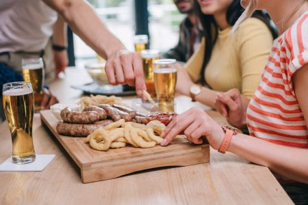 Photo for Partial view of multicultural friends sitting at pub near tray with fried onion rings, sausages and french fries - Royalty Free Image