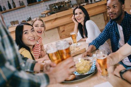 Foto de Vista parcial del hombre sosteniendo vasos de cerveza ligera cerca de amigos multiculturales en el pub - Imagen libre de derechos