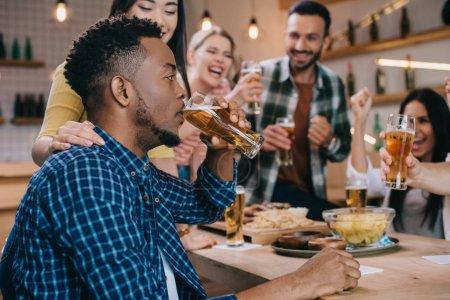 Photo pour Foyer sélectif du jeune homme américain africain buvant la bière légère tout en passant le temps dans le pub avec les amis multiculturels joyeux - image libre de droit