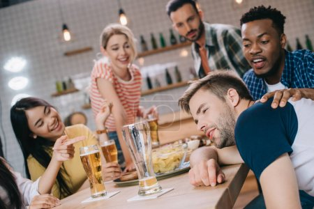 Photo for Cheerful multicultural friends looking at drunk young man in pub - Royalty Free Image