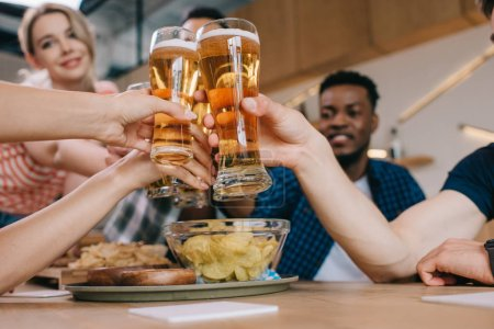 Photo for Selective focus of multicultural friends clinking glasses of light beer in pub - Royalty Free Image
